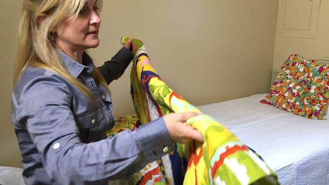 Nashville interior designer and Re-New volunteer Julie Davis on Thursday prepares a child's bedspread for a family moving out of the YWCA domestic violence shelter.