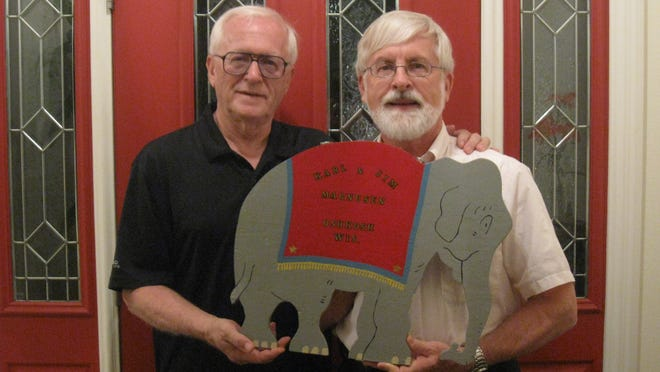 Karl and Jim Magnusen today, holding a sign from the family's handcrafted wooden toy circus. The circus was donated to the Oshkosh Public Museum in August 2014.