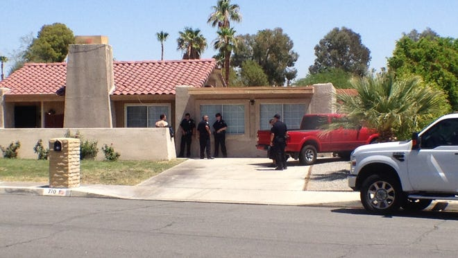 Police gather outside a home in Palm Springs where a man was arrested on suspicion of growing marijuana.