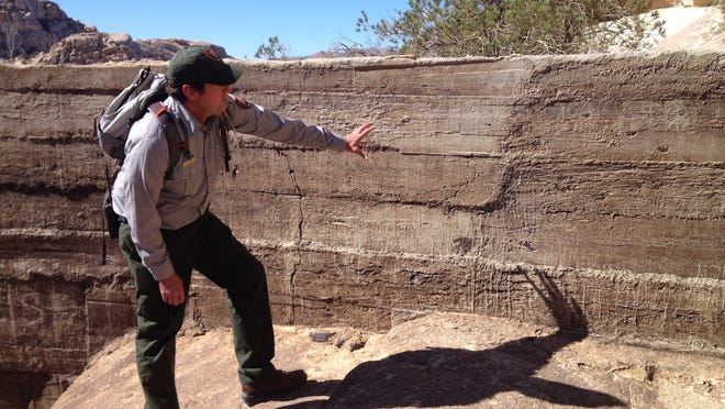 Jay Theuer, cultural resource branch chief at Joshua Tree National Park, examines a portion of Barker Dam where park employees and university researchers have been removing graffiti by dabbing on acrylic paint.