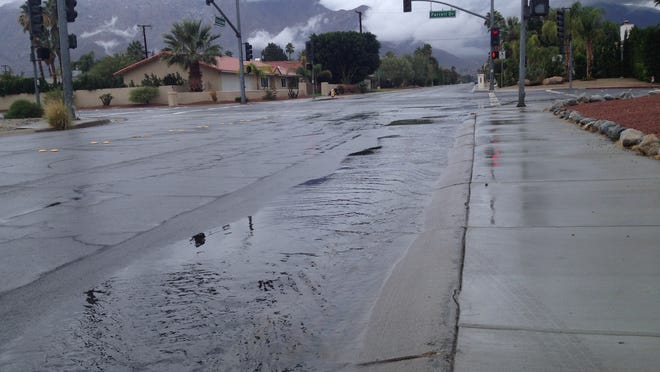 Rain water flows along Via Escuela in Palm Springs Friday morning. Rainfall soaked the desert and was expected to last through Saturday morning.