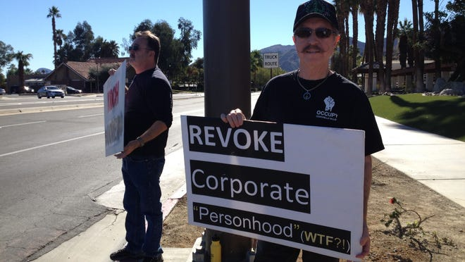Demonstrators stand at the corner of Frank Sinatra Drive and Highway 111 protesting the Koch brothers' conference at the Ritz-Carlton in Rancho Mirage.