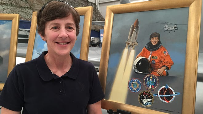 Capt. Wendy Lawrence, U.S. Navy (Ret.) a former NASA astronaut, stands next to her portrait - painted by aviation artist Stan Stokes - at the Palm Springs Air Museum on Friday, Feb. 13, 2015