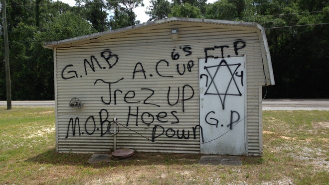 Gang-related graffiti covers a shed. Escambia County Sheriff's Office investigators say there is a strong connection between gangs and many robberies and shootings in the area.