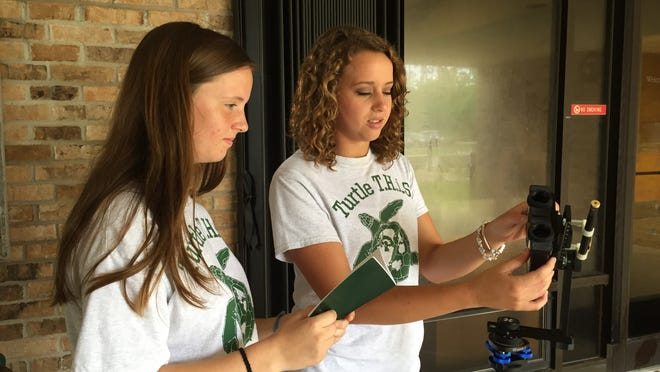 Navarre High juniors and TURTLE T.H.i.S. members Kaylee Christopher, right, and Savannah Koontz demonstrate how newly-hatched endangered sea turtles are instinctually attracted to light. The two are among area teens who are citizen scientists working with the Nation Park Service.