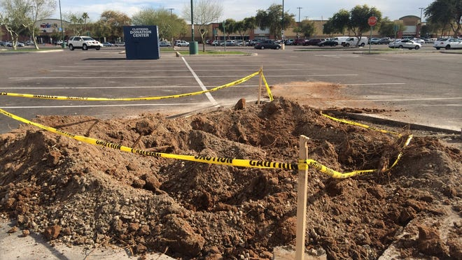 The trees removed at Mesa Grand have left dirt pockmarks across the shopping center's vast parking lot.