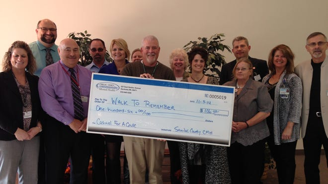 """On behalf of the Sanilac County Community Mental Health employees, executive director Jim Johnson presented a check for $106 to the Building Ties' Walk to Remember Respite Care Fund, in the name of Mary Simon, who retired from Sanilac County CMH after more than 30 years. The money donated by CMH employees is obtained through their """"Casual for a Cause"""" fundraiser. CMH employees are allowed to dress casually every other Friday in exchange for a $3 dollar donation to the """"Casual for a Cause"""" fund."""