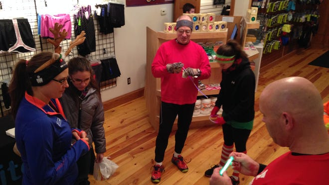 Runners participating in the seven-mile Elite Feet Holiday Light Run arrived at the store early to chat and prepare.
