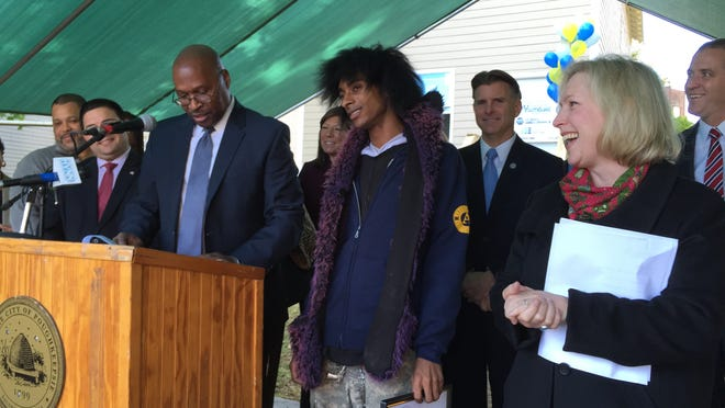 In October, 2014, U.S. Sen. Kirsten Gillibrand, right, hears Robert Wright, executive director of YouthBuild in Poughkeepsie, read a national citation given to William Artist Jr., center, at a ribbon-cuttting at YouthBuild's latest home renovation on Winnikee Avenue, City of Poughkeepsie.