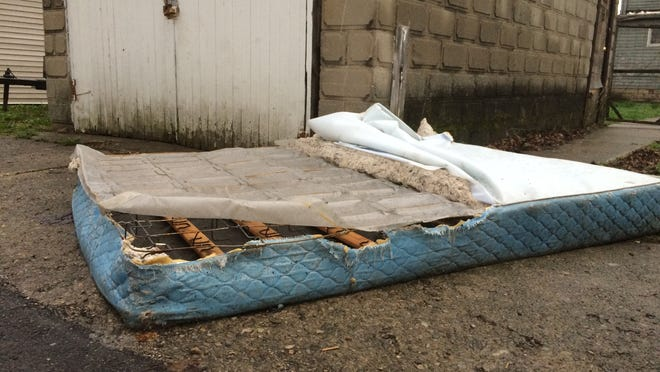 An old mattress has been tossed beside a garage in a Richmond alley.
