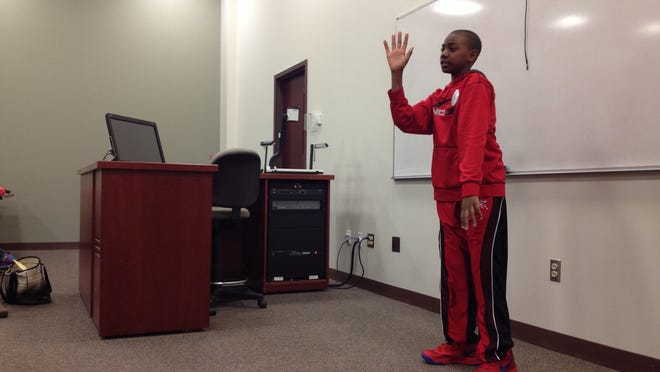 """Kamal Wilson, a sixth-grader at School 25, tells """"The Seven Chinese Brothers"""" on Wednesday at the Rochester School Storytelling Festival at St. John Fisher College."""