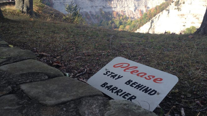 A sign warns park attendees to stay away from the cliff's edge at Letchworth State Park. A 14-year-old boy died Friday after falling 200 feet into the gorge after leaving a park trail.