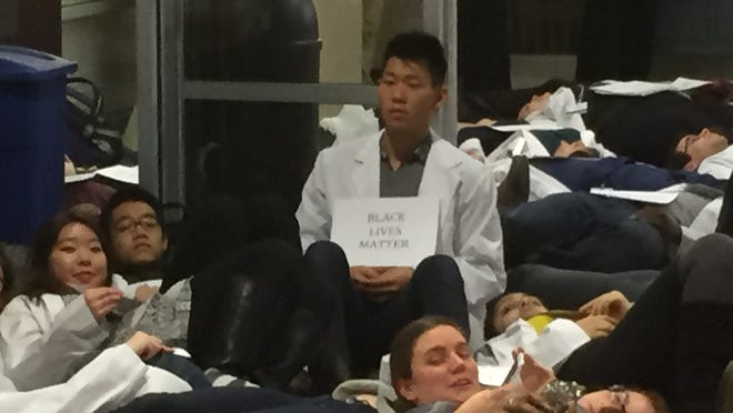 """Timothy Hong, a student at the University of Rochester School of Medicine and Dentistry, takes part in a """"die-in"""" in the admissions office. The event Wednesday was part of a nationwide movement by medical students to draw attention to racial bias as a public health issue."""