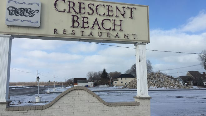 Debris is piled behind the sign of the Crescent Beach Restaurant on Tuesday.
