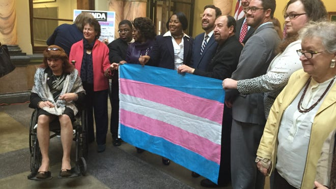 Public officials and LGBT advocates hold up a transgender pride flag at a Thursday news conference.
