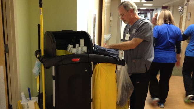 """Dan Myers, Environmental Services Assistant, finishes cleaning a room in the oncology unit at Salem Hospital. Myers. He is one of the instigators of the """"Team Up to Clean Up"""" challenge on the hospital campus."""
