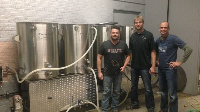 Ben Hart (left), Ben Pattillo and Jason LeBleu with their brewing apparatus at Flying Heart Brewing, at former Bossier City Fire Station 6 in the 700 block of Barksdale Boulevard in Bossier City. Hart holds a cattle brand from the family ranch after which their business was named.
