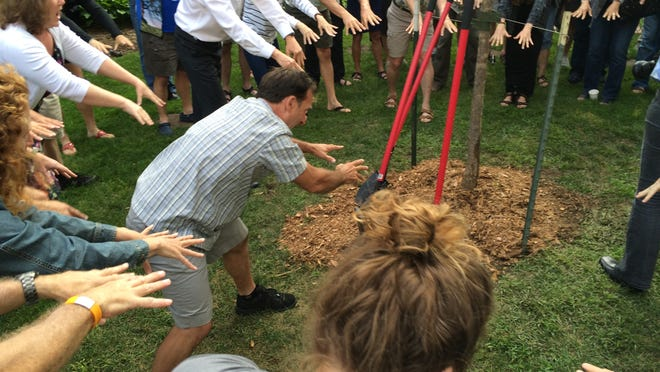 """People attending a tree-planting ceremony at the University of Wisconsin-Stevens Point on Tuesday as part of the STIHL Tour des Trees participate in a """"ceremony"""" to help the tree planted on campus grow."""