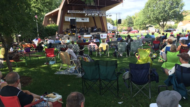People seated in Pfiffner Pioneer Park enjoy the Riverfront Jazz Festival.