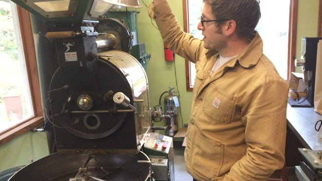 Jared Linzmeier, founder of Ruby Coffee Roasters, stands next to the coffee roaster for his business, located in his home in Amherst Junction.