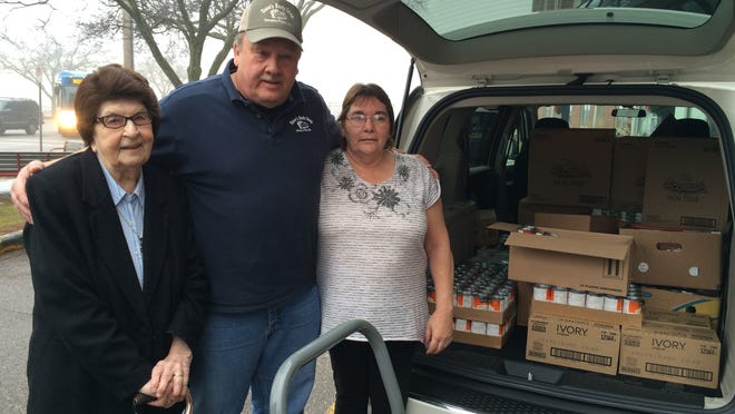 Dave Suchon, owner of Dave's Body Shop, center, drops off a truckload of items, including food and toiletries, totaling about $1,300 to the Hi-Rise Manor on Dec. 15. Also pictured are Sister Leone Juszczyk, who helps coordinate the drive, and Hi-Rise Manor resident Sherry Elmore. Suchon has been making the annual donation since 1988.