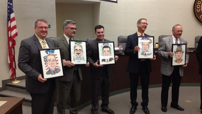 Members of the Tulare County Board of Supervisors and county Chief Administrative Officer, Jean Rousseau, second from right, hold up caricatures given to them by county Resource Management Director Jake Raper prior to his retirement next week.