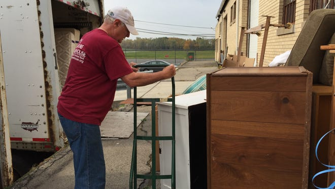 A volunteer moves furniture at the Furniture Sharehouse, a non-profit that collects gently-used furniture from the public and redistributes it free-of-charge to families in need.