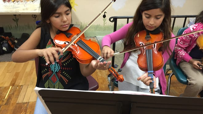 Chantel Godoy, left, and Gabriella Barragan practice the violin at Songcatchers.
