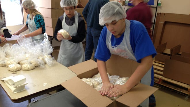 Nicole Lazar, left, Hunter Guinn and Jake Fisher pack rice for delivery at the Food Bank for Westchester. The Food Bank and the Westchester Coalition for the Hungry and Homeless are set to merge officially Friday.