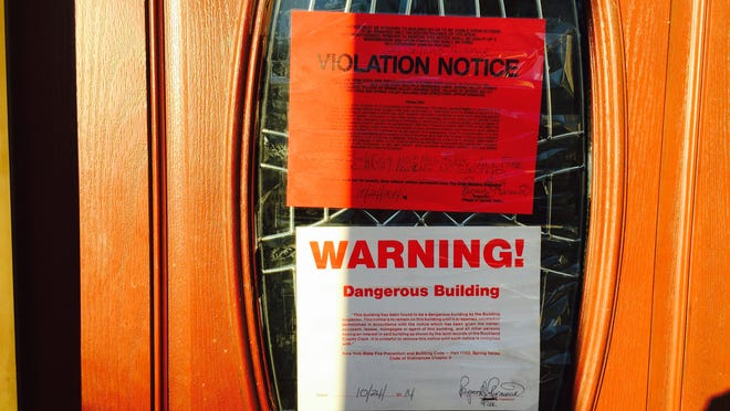 Violation notice on a Spring Valley home following a fire last year.