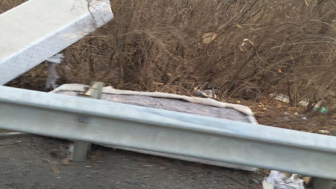 DelDOT workers have cleaned up a long string of debris, highlighted by two mattresses, covers the ground near the northbound Interstate 95 exit off Del. 141.