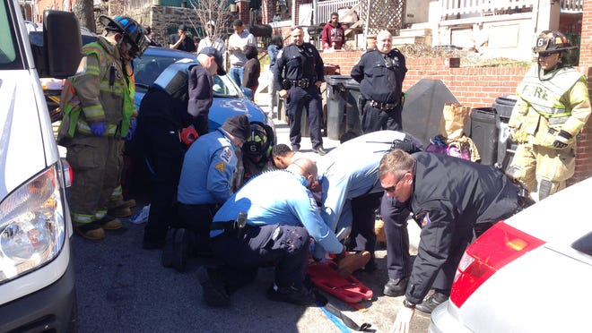 Rescuers prepare to move an 11-year-old boy who suffered head and leg injuries Sunday when he was hit by a car in Wilmington.