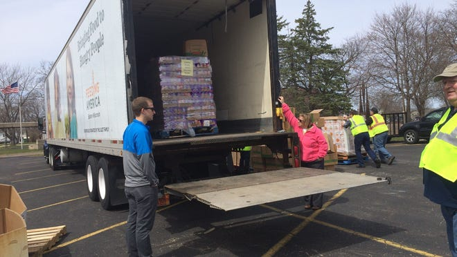 Volunteers wait for a pallet of food off the Feeding America Mobile Food Pantry truck Wednesday afternoon in Wisconsin Rapids.