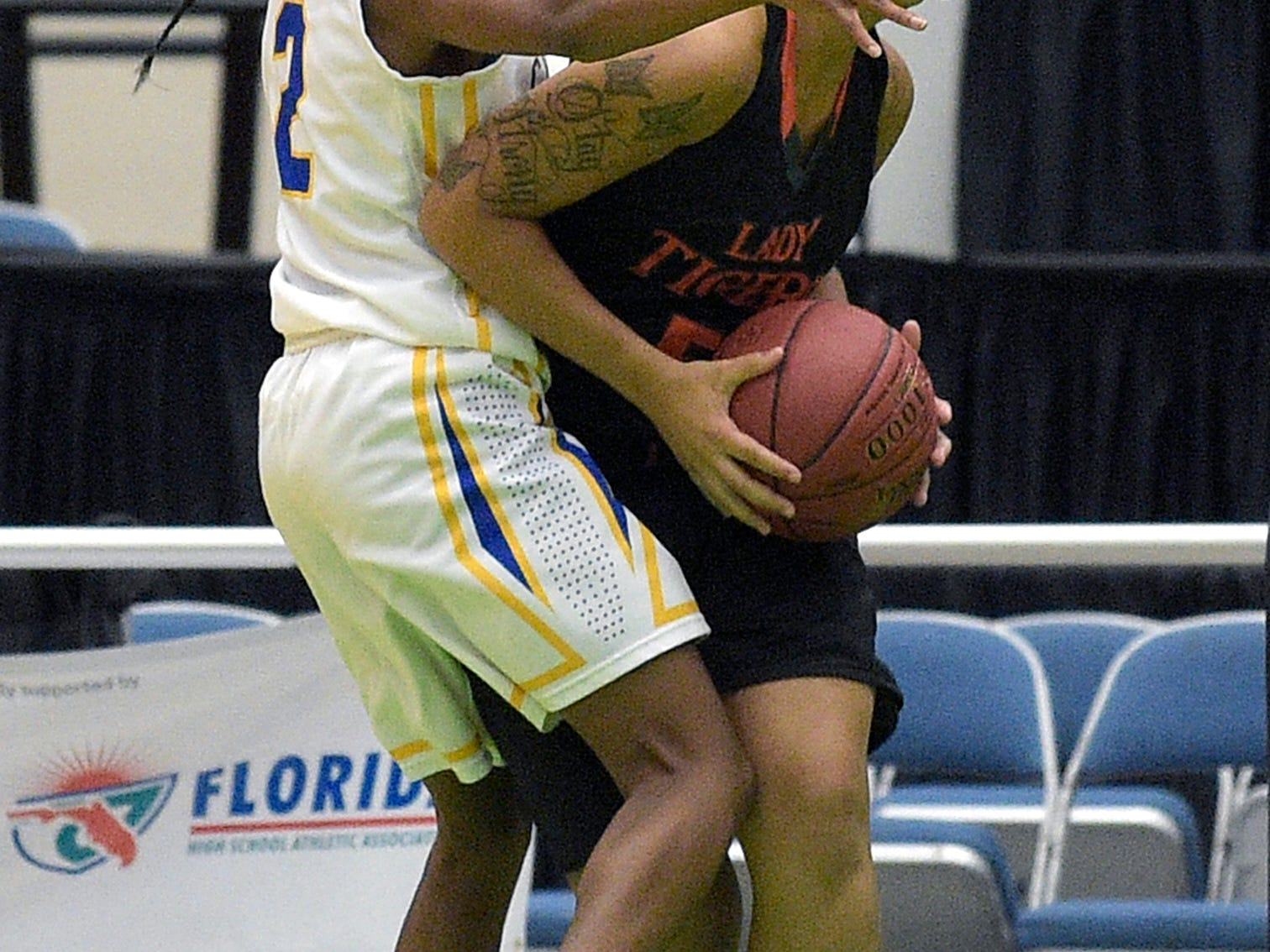 Dunbar's Alicia Johnson grabs a rebound in front of Cardinal Newman's Anise Williams during Tuesday's girls basketball Class 4A semifinal game in Lakeland. Dunbar won 61-39 and will play Orlando Lake Highland Prep today for the title.