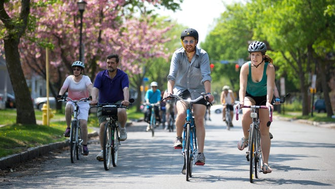 Derek Crowe and Amber Odhner ride down Troup Street on their bicycles during a historical tour of sites in Rochester that have been significant in US and local social movements on May 10, 2015.