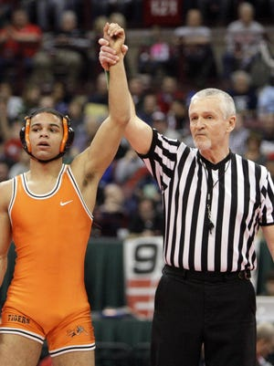 A referee raises the arm of Massillon's Ivan McClay after he won his first state championship in 2013.