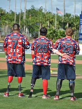 Wounded Warrior amputee softball team members pay respect during the National Anthem.