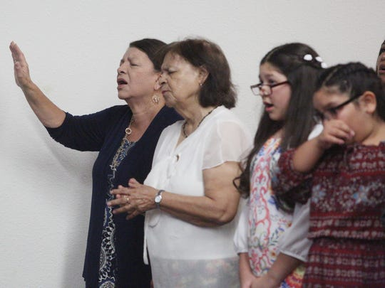 At far left, the wife of Pastor Frank B. Amado, Lucia Amado, prays during her husband's memorial service at The Potter's House Christian Fellowship Church in Indio.