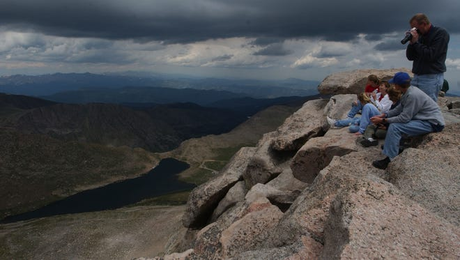 A group pf people take in the sights at the top of Mount Evans.