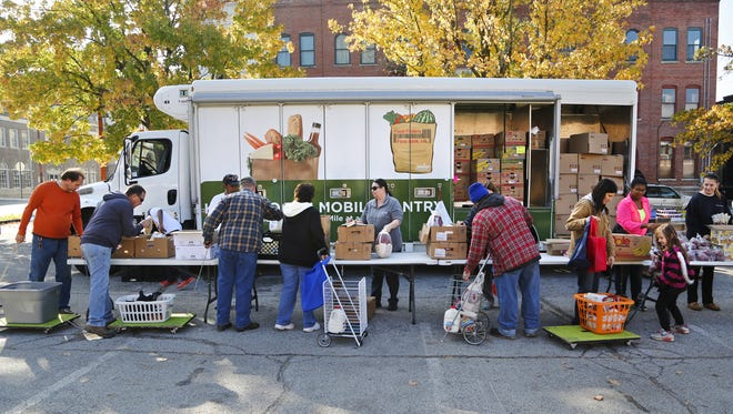 Patrons receive a wide variety of foods as Food Finders Food Bank opens its mobile pantry in the Journal & Courier's parking lot Saturday, October 25, 2014, in downtown Lafayette. Several J&C employees volunteered for the event as part of Make A Difference Day.
