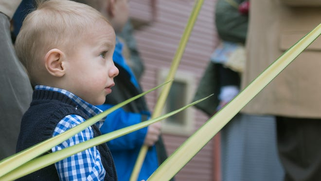 Maximillian Ebert, age 2, watches the Palm Sunday procession during Mass at Saints Peter and Paul Roman Catholic Chapel in York Sunday March 20, 2016.