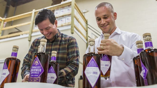 State Rep. Trey Paradee, D-Cheswold,  (left) and Rep. Jeff Spiegelman, R-Clayton, cork and label bottles of Painted Stave's  bourbon whiskey in 2015. The distillery led the push in support of H.B. 373.