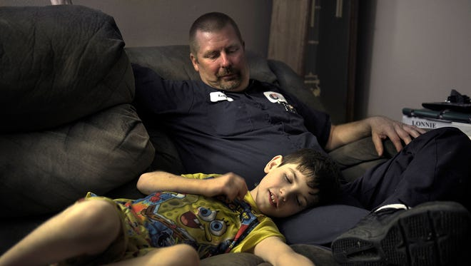 Jonathan Cunningham lies on the couch with dad Kelly Cunningham. Jonathan is in a program to deal with severe psychological problems that are tied to a variety of drugs that were in his system at birth. The Cunninghams did not know about Jonathan's medical issues when they adopted him.