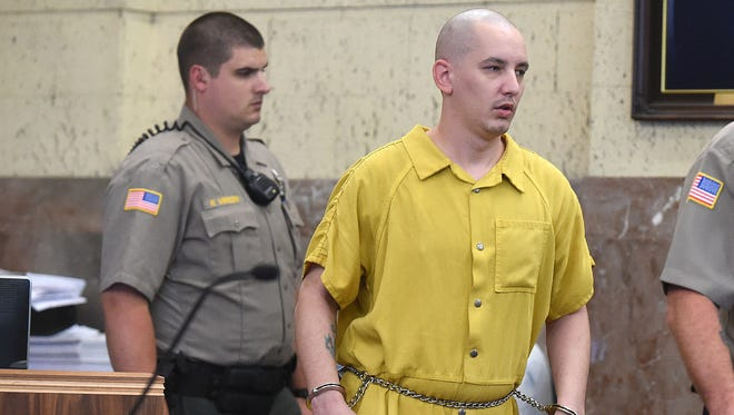 Linn County Sheriff's deputy Nick Vinson escorts Zachary Lee Burghart, 28, into a Linn County Courtroom Thursday, June 11, 2015. Burghart, who earlier this week pleaded guilty to burning down the cafeteria at South Albany High Schoo, was sentenced to 16 1/2 years in prison for that arson, an arson outside a neighboring residence and violating his probation violation of earlier arson convictions in 2014. (Mark Ylen/Albany Democrat-Herald via AP)