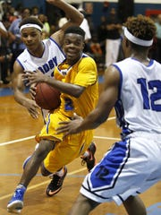 Rickards' Javon Wooten drives into the lane between Godby's Montre Edwards, left, and Montreal Edwards during their game at Godby High School on Friday.