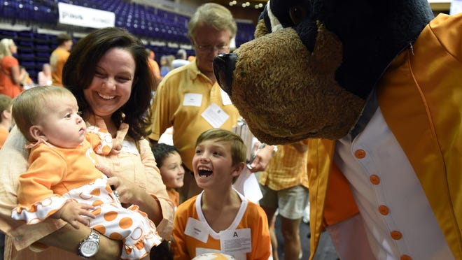 Molly Tarpy, holds her daughter Mary Holland, 4 months old, up for UT mascot Ole Smokey as Jordan Tarpy joins in the fun at the UT All-Sports picnic on Tuesday.