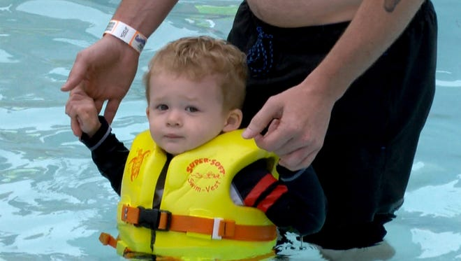 Sullivan Schwenck, 2, Bayville, hangs onto his father Bill's hands as they take part in the World's Largest Swimming Lesson at the Breakwater Beach water park in Seaside Heights Thursday, June 21, 2018.  This event is intended to show people how important it is for children to learn how to swim.