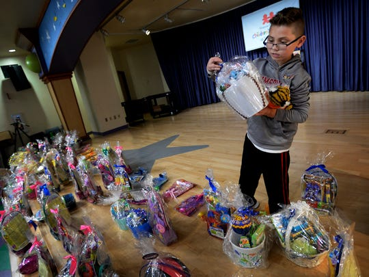 Jackson Agee, 9, picks out a Easter basket during an Easter egg hunt hosted by the FBI and Monroe Carell Jr. Children's Hospital on Thursday, March 29, 2018, in Nashville Tenn. The children used law enforcement robots to hunt for the eggs at Vanderbilt to give them a brief respite from their hospital stays.