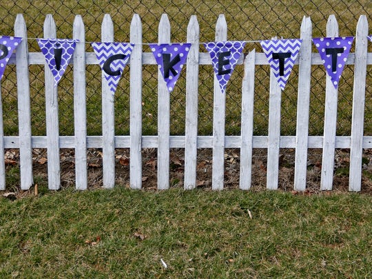 "A sign of support, a picket fence with the name ""Pickett"" on it, is seen on a fence at White Lick Elementary School before the funeral procession of Boone County Deputy Jacob Pickett passes the school in Brownsburg, Friday, March 9, 2018.  Deputy Pickett's wife, Jennifer Pickett works at the school.  Deputy Pickett was fatally shot the morning of Friday, March 2, while chasing a man fleeing from police."