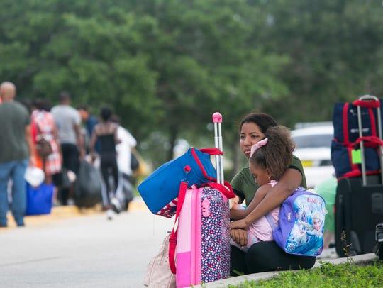 Ashly Saldana, 16, holds her little sister Yasily Rivera,
